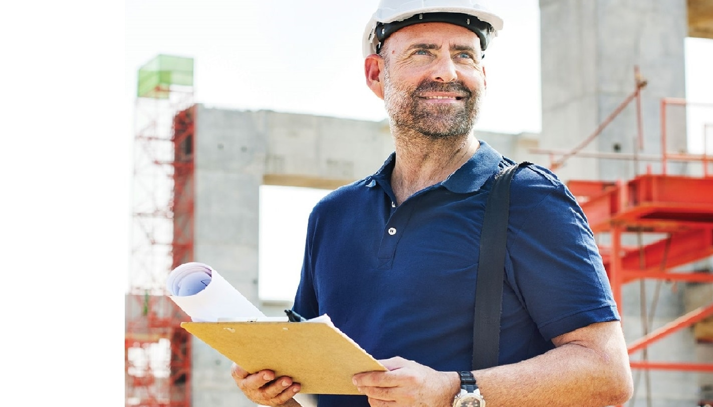 Man holding documents and smiling on jobsite looking into distance